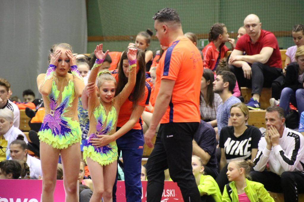 rozgrzewka akrobatów przy pomocy trenerów